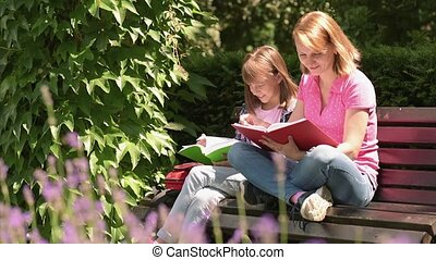 Mother and daughter reading books - Mother and her daughter...