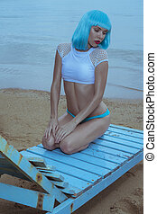 Sexy beautiful woman in modern futuristic style posing on the damaged wooden blue sunbed