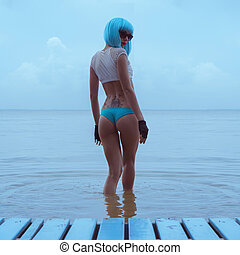 Sexy woman in modern futuristic style with blue wig posing in the sea