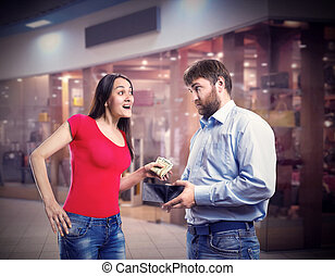 Woman taking money from husbands purse in the shopping mall