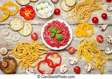 Pasta tomato basil eggplant meat minced onion wood background