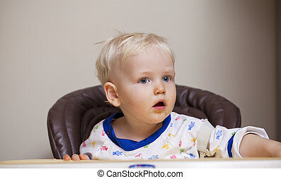 Two year baby boy eating in a highchair at home - Portrait...