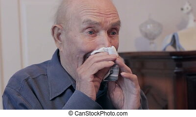 Old man wiping his nose with a handkerchief. Senior sneezes...