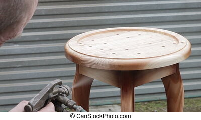 Carpenter is covering stool by lacquer. Furniture varnishing...