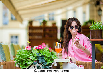Portrait of young beautiful woman sitting in a cafe outdoor...
