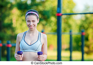 Beautiful young woman working out with weights outdoors...