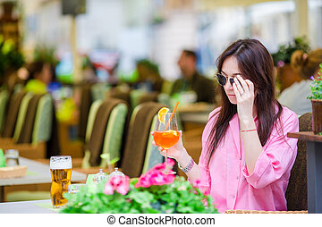 Young beautiful woman sitting in a cafe outdoor drinking...