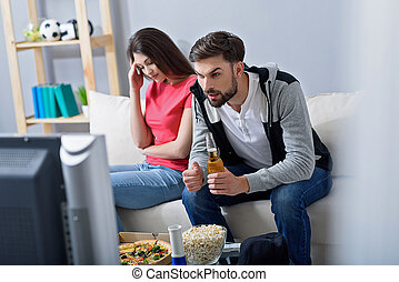 Man and woman watching tv on couch - Enjoying interesting...