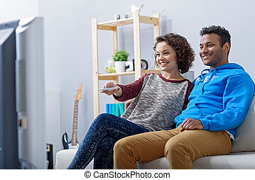 Man and woman watching tv on couch - Changing channel....