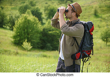 Cheerful male tourist relaxing in meadow - Young man is...