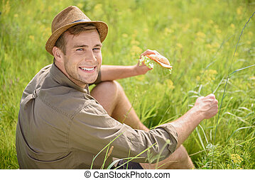Cheerful guy having lunch on meadow - Happy young man is...