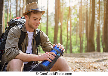 Handsome male traveler resting in nature - Relaxed tourist...