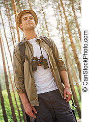 Cheerful man hiking in nature - Relaxed young tourist is...