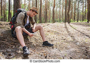 Cheerful male tourist cutting wood - Skillful young man is...