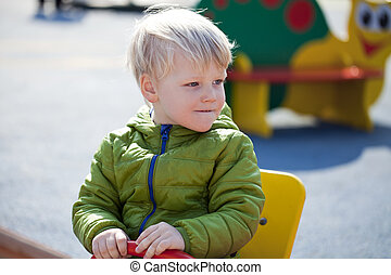 A three-year a little boy sitting on a swing at the...