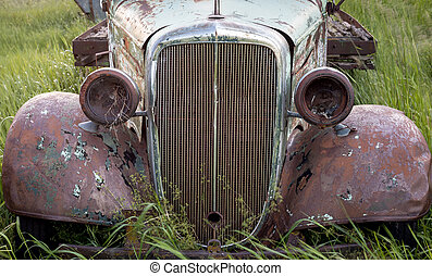 Farm truck left to rust and rot - Grill and headlights of an...