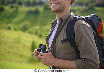 Young traveler enjoying vacation on field - Happy male...