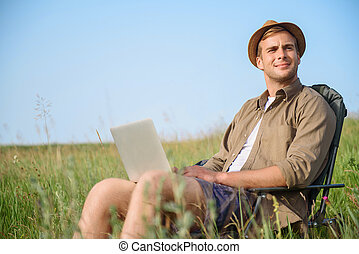 Healthy guy relaxing on meadow with laptop - Relaxed young...