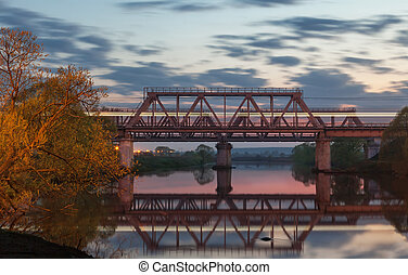 Railway bridge over the river at sunset with blurred light...