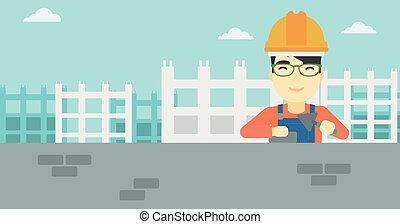 Bricklayer with spatula and brick. - A n asian bricklayer in...