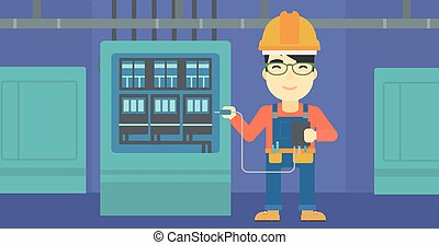 Electrician with electrical equipment - An asian man in...