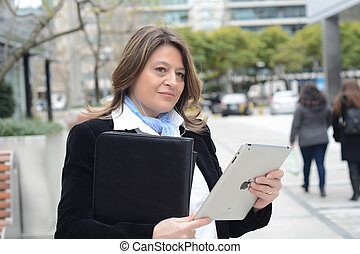 Business woman listening to music with her tablet Outdoors