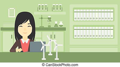 Woman working with model wind turbines on table. - An asian...
