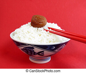 Bowl of white rice with ume and red chopsticks on red...