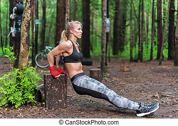 Fit woman doing triceps dips at park. Fitness girl...