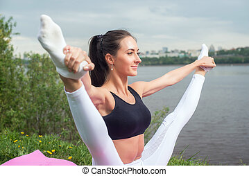 Woman holding legs apart doing exercises aerobics warming up...