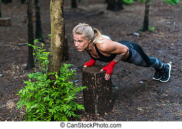 Muscular woman doing push-ups at park street work out.