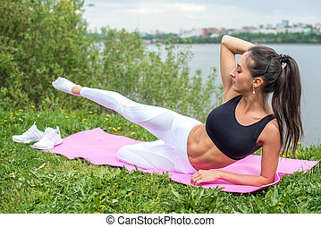 Woman in a yoga pose with her arm reaching overhead raising...