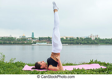Fit woman making yoga in shoulderstand pose exercising in...