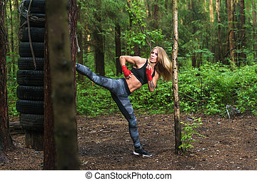Fit girl beat high leg side kick working out outdoors. Woman...
