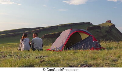 Young couple rest in a camp in outdoor nature scenery during...