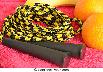 Fresh fruit and jumping rope on red towel - Fresh fruit...