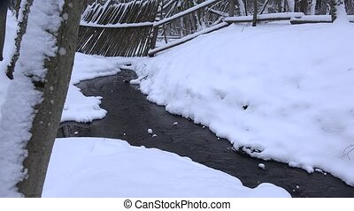 Winter creek flow through wooden fence in snowy park 4K -...