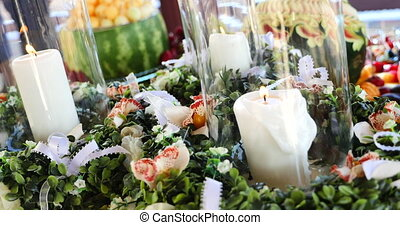 candles in glass among the flowers