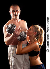 Fitness couple, man doing workout while embraced by a...