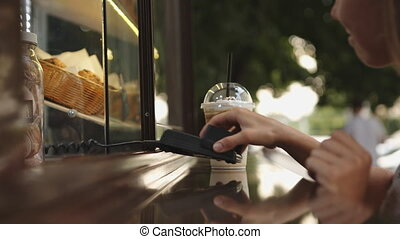 Woman bought a coffee and pays with a credit card - Young...