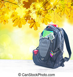School backpack with supplies on white desktop, fall tree...