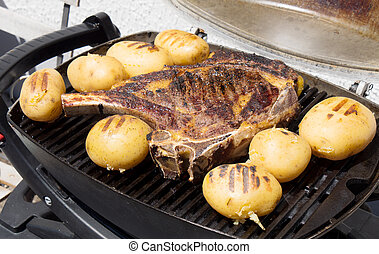 rib of beef with potatoes on the barbecue