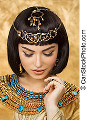Beautiful Egyptian woman like Cleopatra on golden background...