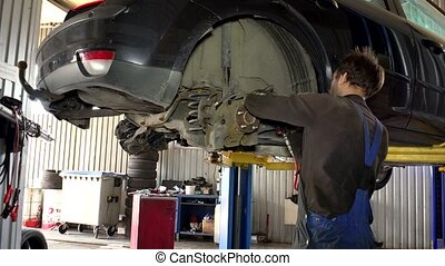 Auto mechanic working at auto repair shop tilt down - Auto...