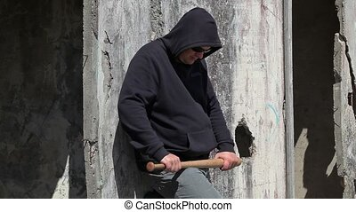 Man with a baseball bat near wall