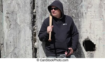 Man with a baseball bat watching near wall