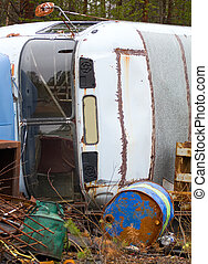 Fragment of trucking dump. Old bus and empty barrels out of fuel