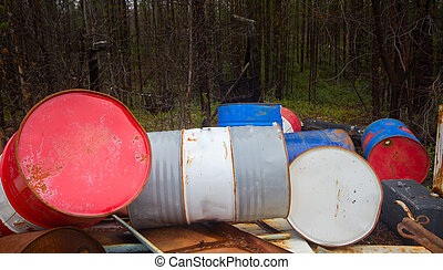 Height of mismanagement and irresponsibility. Colorful empty barrel of fuel left in forest