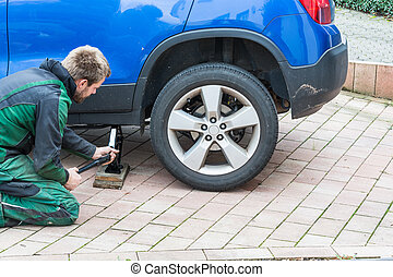 Replace summer tires against winter tires - Young man...