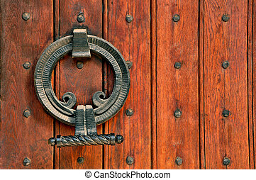 Church doorway with wooden doors and intricate metal hinges...